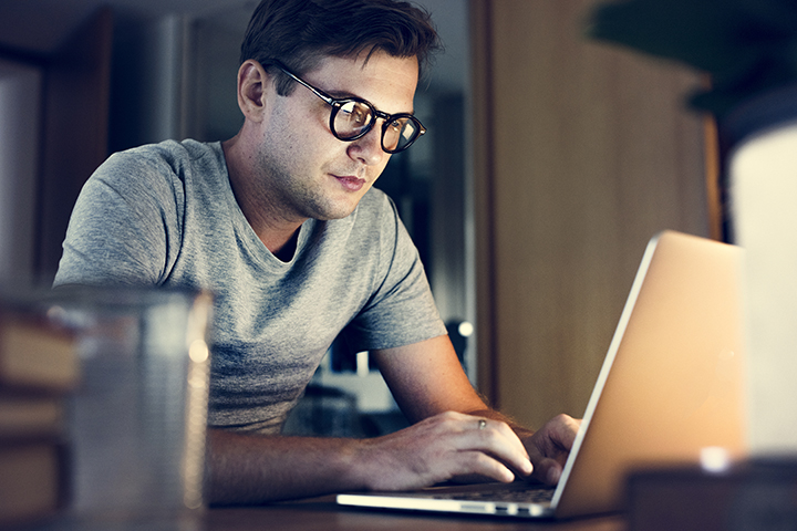 Homem trabalhando no computador fazendo boas práticas da programação SQL