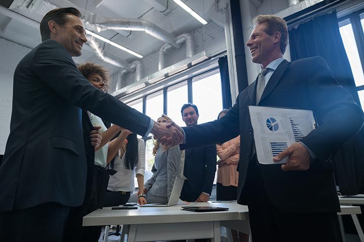 Homens de negócio apertando as mãos para benefícios no relacionamento