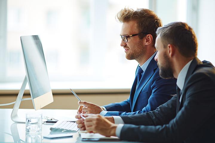 Homens trabalhando no computador usando ITIL 4