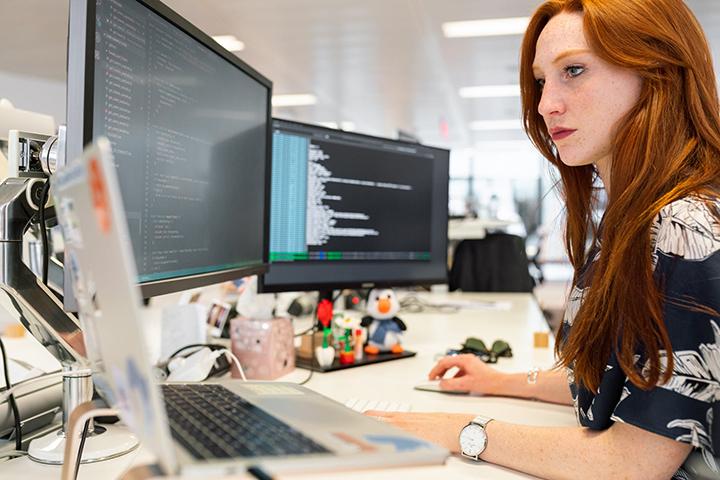 Mulher trabalhando em computador utilzando software e ferramentas de TI