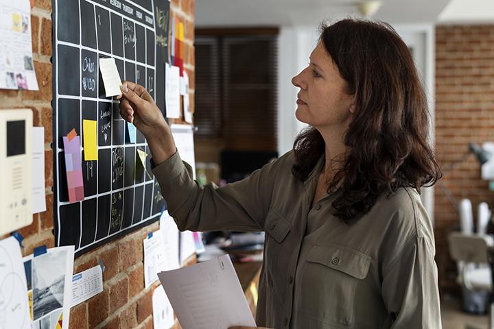 Mulher usando post it em quadro para facilitar trabalho de modo framework
