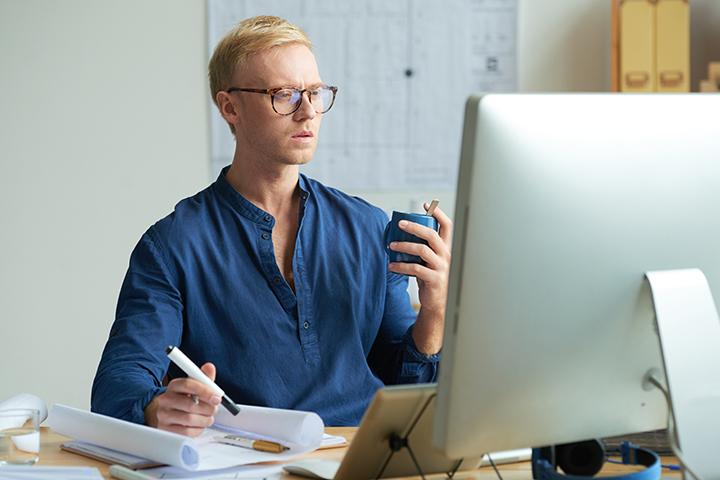 Product Owner homem acessando computador e fazendo anotações