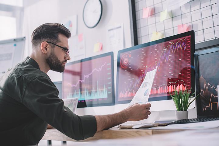 Homem acessando computador e observando relatório de verificação estratégica de riscos