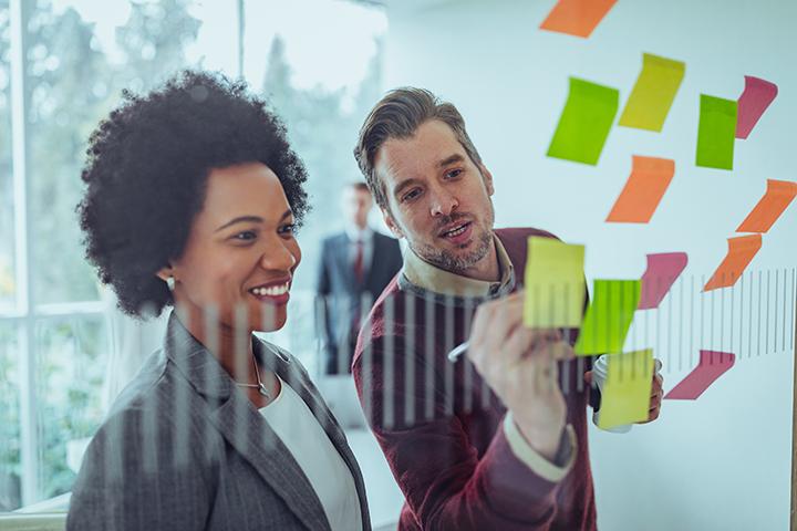 Homem e mulher utilizando framework em ambiente de trabalho