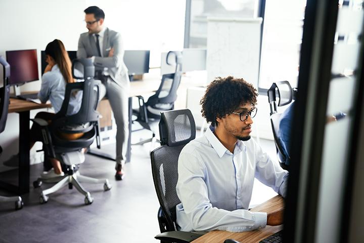 Homem trabalhando em projeto de ti e colegas ao fundo discutindo sobre ética na profissão