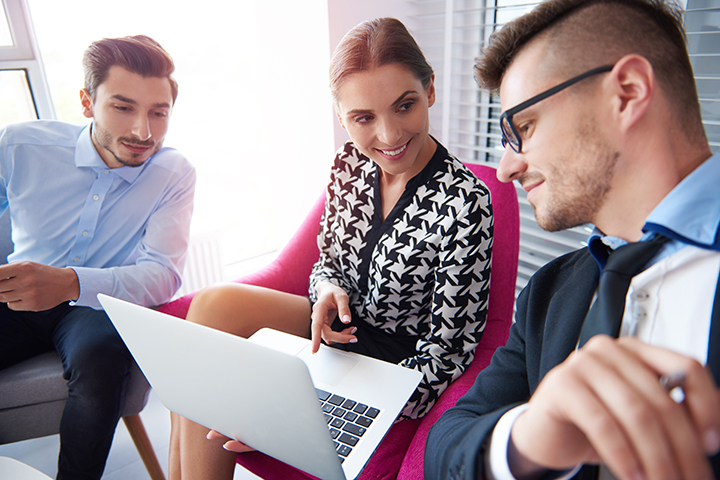 Homens uma mulher acessando laptop e conversando sobre Exame ISO/IEC 20000