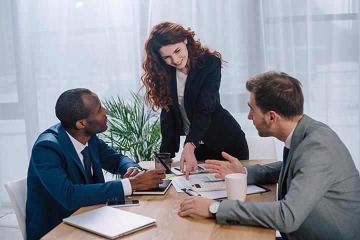 Mulher conversando com dois colegas de trabalho sobre a prática do Lean IT