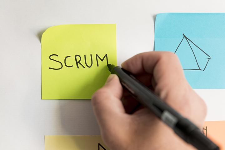 Mão escrevendo scrum em um postit