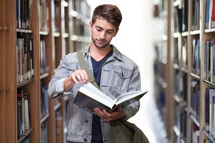 Rapaz lendo livro na biblioteca da faculdade