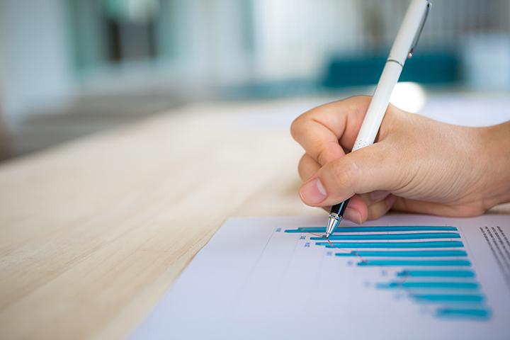 Mão de uma pessoa escrevendo sobre gestão de projetos da ITIL 4