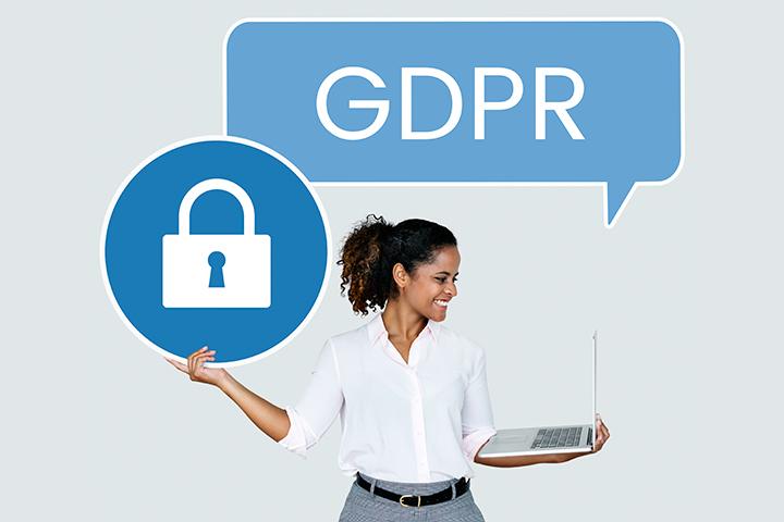 Mulher com laptop na mão satisfeita com sua segurança de dados pela GDPR