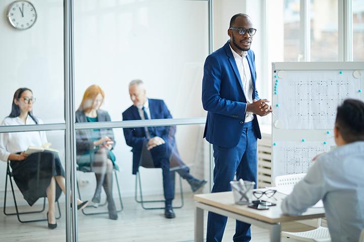 Homem conversando com outro homem sobre modelo de gestão VeriSM e cercado de executivos