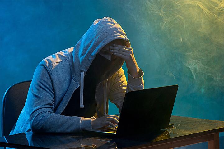 Hacker usando laptop para acessar sistemas para proteger do attacker
