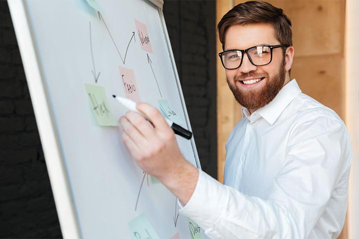 Homem arquiteto de soluções de ti escrevendo em lousa branca