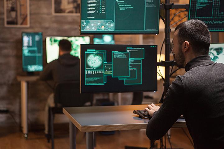 Homens trabalhando em computadores fazendo a proteção de dados GDPR
