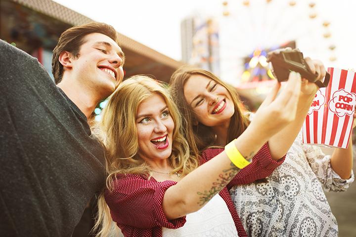 Pessoas felizes no parque de diversão fazendo selfie devido a inserção da ITIL